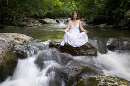 Belle jeune femme méditant entourée par les eaux purificatrices d'un ruisseau de montagne Banque d'images
