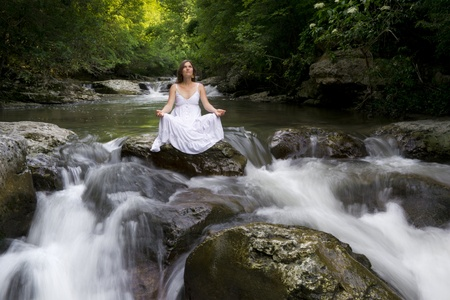 purifying: Beautiful young woman meditating surrounded by the purifying waters of a clear mountain stream Stock Photo