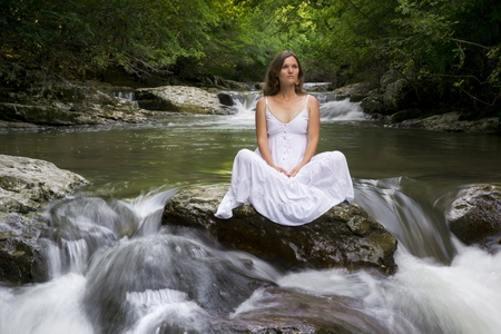 Beautiful young woman sitting on a rock surrounded by the purifying waters of a clear mountain stream photo