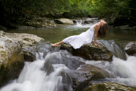 purifying: Beautiful young girl enjoying the purifying herself in the clear water of a mountain stream
