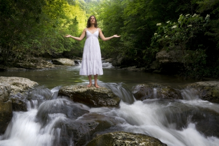 Beautiful young girl enjoying the purifying herself in the clear water of a mountain stream photo