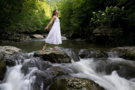 inspirerend: Mooie jonge meisje genieten van de zuiverende zich in het heldere water van een bergbeek Stockfoto