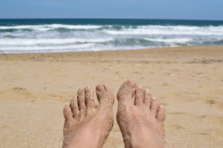 Female feet relaxing on the sandy beach overlooking the blue sea photo
