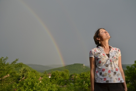 Beautiful young woman looking at the rainbow on the sky after the rain has passed and the sun has returned photo