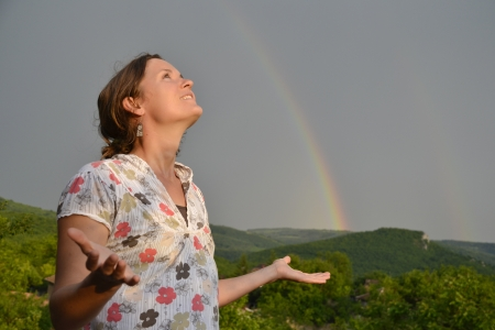 Beautiful young woman looking at the rainbow on the sky after the rain has passed and the sun has returned Stock Photo