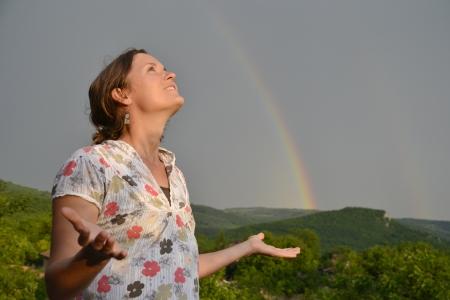 Belle jeune femme cherche à l'arc en ciel sur le ciel après la pluie est passée et que le soleil est de retour Banque d'images - 14166165