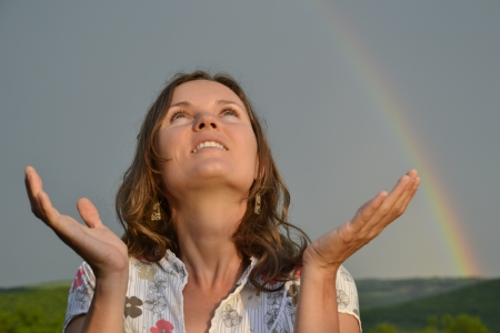Beautiful girl looking at sun sky after the rain with hands open in gratitude Stock Photo
