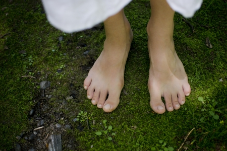 A young girls bare feet feeling the softness of the green moss connecting with the earth
