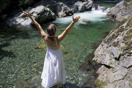 purifying: Beautiful young woman enjoying the purifying waters of a crystal clear mountain spring