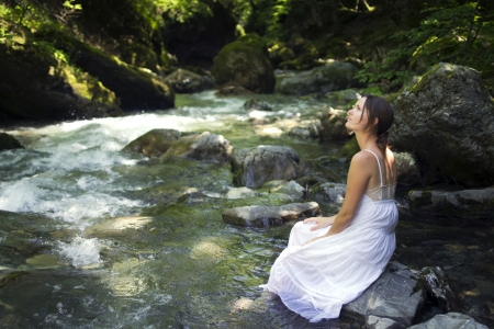 Beautiful young woman enjoying the pure waters of a mountain river in the forest photo