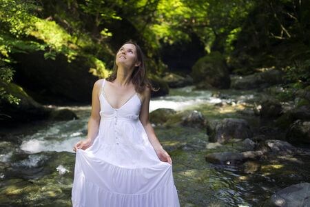 wet dress: Happyl young woman enjoying the pure waters of a mountain river in the forest