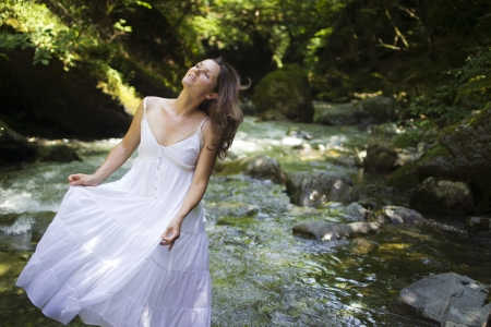 Happyl young woman enjoying the pure waters of a mountain river in the forest Stock Photo - 14166153