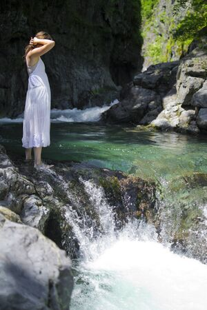 Beautiful young woman enjoying the purifying waters of a crystal clear mountain spring photo