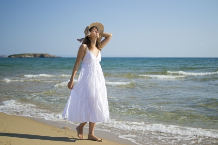 Beautiful young woman walking on sandy beach wearing a hat and a white dress enjoying the sun