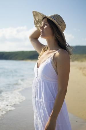 bulgaria girl: Beautiful young woman walking on sandy beach wearing a hat and a white dress enjoying the sun