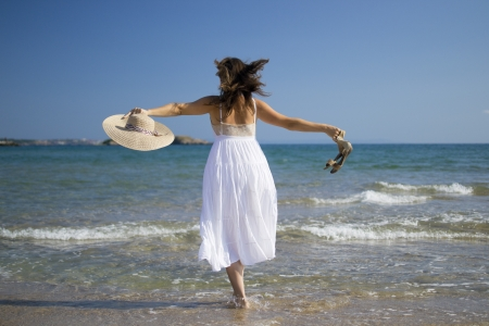 Beautiful young woman playing on sandy beach wearing a hat and a white dress enjoying the sea waves photo