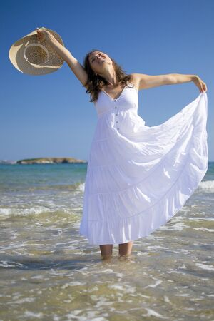 Beautiful young woman wearing a hat and a white dress playing with the waves of the sea Stock Photo - 14786915
