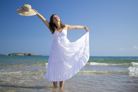 Beautiful young woman wearing a hat and a white dress playing with the waves of the sea Stock Photo - 14786892