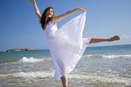 Beautiful young woman wearing a hat and a white dress playing with the waves of the sea Stock Photo - 14786914