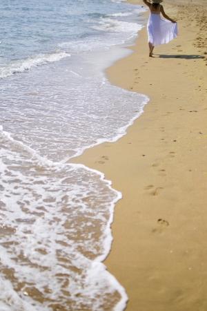Young woman walking on sandy beach wearing white dress photo