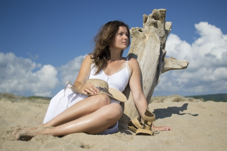 beach scene: Beautiful young woman lying on sandy beach wearing a hat and a white dress enjoying the sun