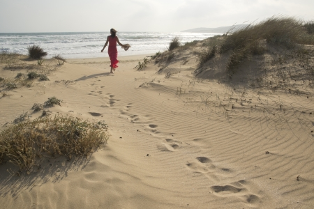 in distance: Beautiful young woman walking through the sand dunes towards  beach