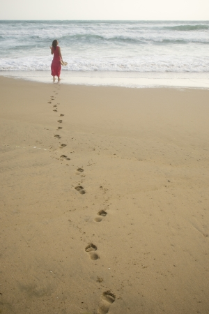 Beautiful young woman walking on the beach towards the sea leaving footprints