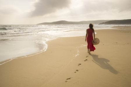 woman beach dress: Young woman walk on an empty wild beach towards celestial beams of light falling from the sky