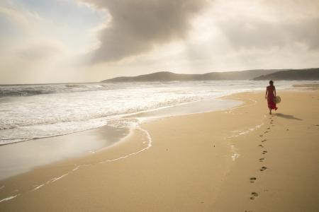 Mujer joven caminando en una playa salvaje vacío hacia las vigas celestiales de luz que caen del cielo Foto de archivo