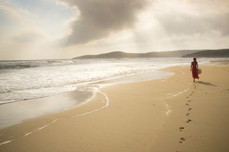 footprints in the sand: Young woman walk on an empty wild beach towards celestial beams of light falling from the sky