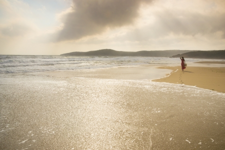 bulgaria girl: Young woman walk on an empty wild beach towards celestial beams of light falling from the sky