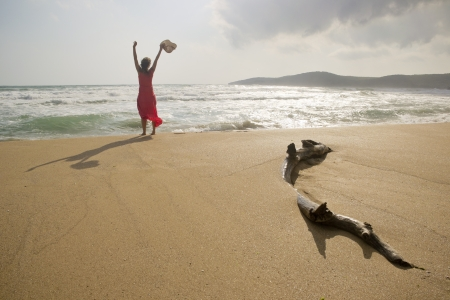Beautiful young woman raising her arms with joy on a beautiful wild pristine sandy beach