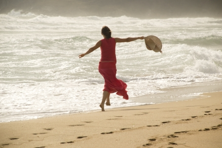 bliss: Beautiful young happy woman wearing red dress playing with the waves on a sandy beach Stock Photo