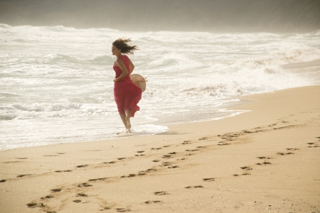 Beautiful young happy woman wearing red dress playing with the waves on a sandy beach Stock Photo - 14786887