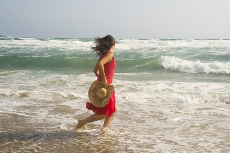 Beautiful young happy woman wearing red dress playing with the waves on a sandy beach Stock Photo