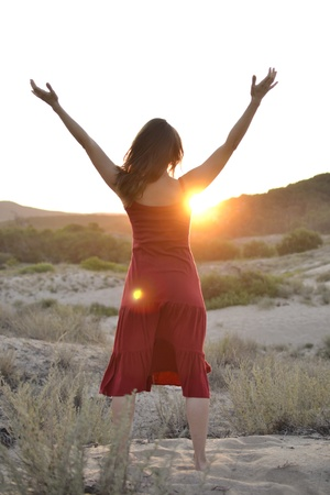 affirmation: Beautiful young woman raising her arms to greet the sun