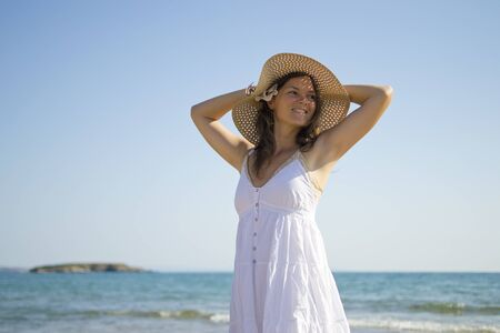 Happy smiling young woman in a white dress next to the sea Stock Photo - 16012036