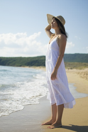 Beautiful young woman wearing a white dress and straw hat looking out to sea  Stock Photo - 16012050