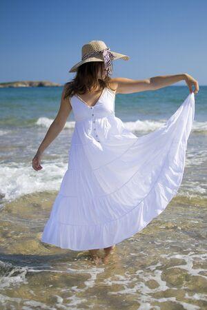 Joyful beautiful young woman wearing a white dress playing in the sea Stock Photo - 16012042