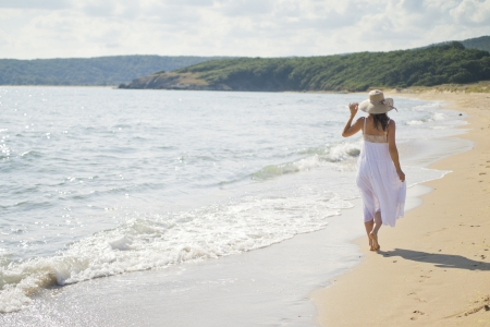 woman beach dress: A beautiful young woman takes a relaxing walk along a sandy beach Stock Photo