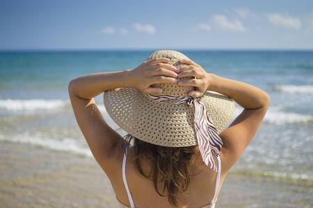 mujer mirando el horizonte: Joven y bella mujer con suavidad mientras sostiene a su sombrero de verano con vistas al mar