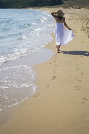 A beautiful young woman in a white dress walks along the beach photo