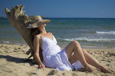 relaxes: Joven y bella mujer se relaja mientras que se sienta en la playa