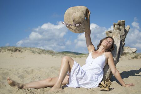 Beautiful young woman stretches whilst leaning on some driftwood on the beach photo
