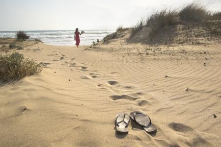 bulgaria girl: A beautiful woman walks barefoot through sand dunes towards to sea leaving her flip flops behind