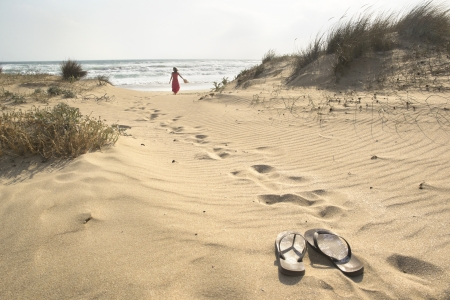 flops: A beautiful woman walks barefoot through sand dunes towards to sea leaving her flip flops behind
