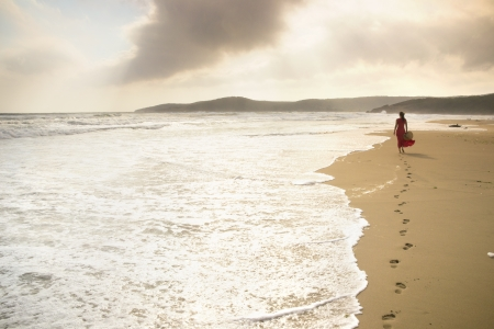 Beautiful young woman walks along the surf on a pristine sandy beach photo