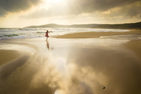 Majestic beach with dramatic reflections and girl running freely