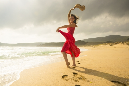 Beautiful happy young woman dancing on a sunny sandy beach Stock Photo