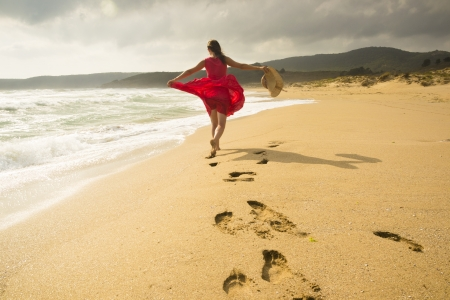 Beautiful happy woman running freely on the beach Stock Photo